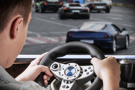 gamer driving autosimulator on the background screen with the game Archivio Fotografico