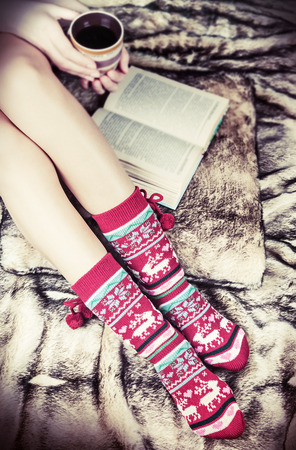 female legs in Christmas socks with a book and a cup of coffee. artificial fur on the floor. toning image photo