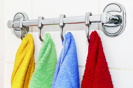 colored towels hanging on the rack in the bathroom. focus on green-blue towel photo