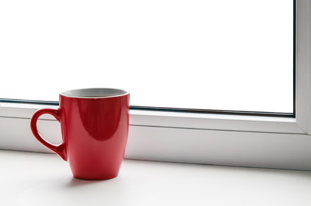 red cup on the windowsill isolated on white background photo