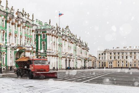 snow removal on the Palace Square in St. Petersburg. Russia, winter, dawn. Focus on the central entrance of the palace, on the left