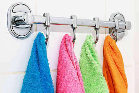 colored towels hanging on the rack in the bathroom photo