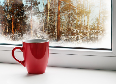 red cup of coffee on the windowsill on the background of the winter forest photo