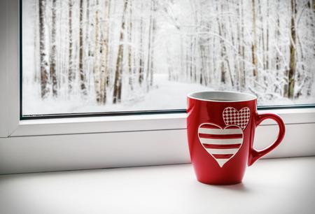 estado del tiempo: taza con corazones en el fondo de un paisaje de invierno
