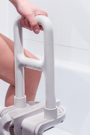 handrail: hand holding the handrail in the bathroom. Focus on the handrail. Stock Photo