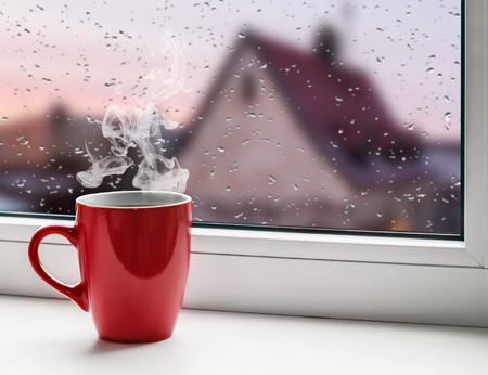 red cup of coffee on the windowsill on the background city roofs in the rain