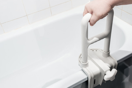 hand holding the handrail in the bathroom. Focus on the handrail. Stock Photo