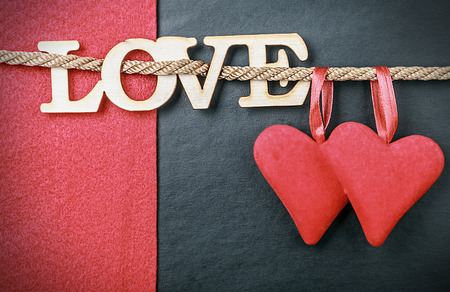 hearts made of felt and the word love made of wood. Can be used for congratulation to the holiday Valentine's Day and Mother's Day Foto de archivo