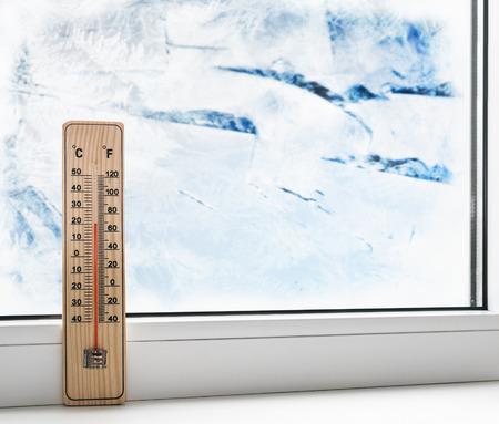 term�metro: Term�metro en una ventana congelada y el fr�o exterior. Foto de archivo