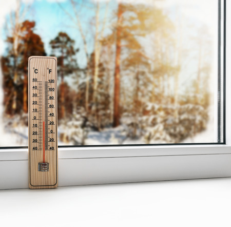 Thermometer on a frozen window and cold weather in spring forest