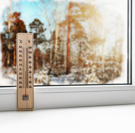 clima: Termómetro en una ventana congelada y el clima frío en el bosque de la primavera