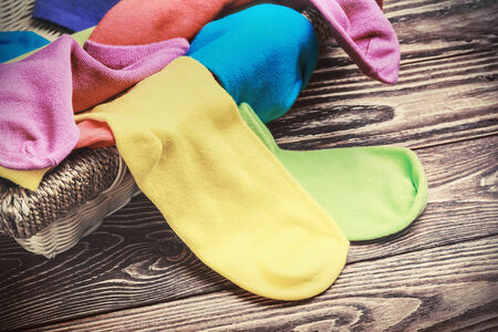 white socks: scattered multi-colored socks and laundry basket on a wooden background. toned photo