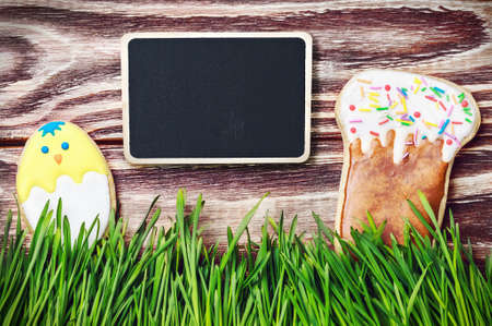 Easter homemade gingerbread cookie over wooden table and black board for congratulations photo