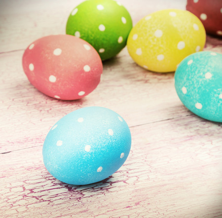 pascha: colored Easter eggs on wooden background. Focus on a blue egg. toned photo