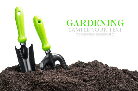 garden tools in soil isolated on white background. The text is an example and can be easily removed Stockfoto