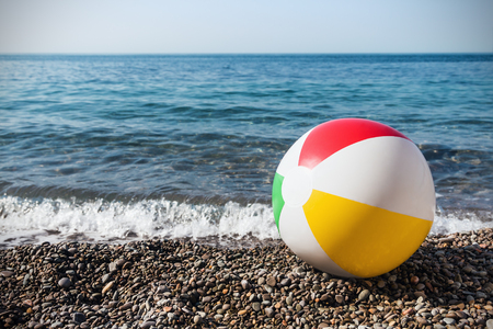 white beach: childrens inflatable ball on the beach against the sea Stock Photo