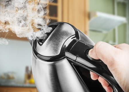 Stainless Steel Electric Kettle in hand on the background of the kitchen. focus on the lid of the kettle Standard-Bild