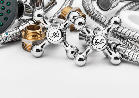 plumbing and tools in a light background. Focus on plumbing taps