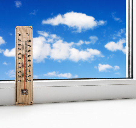 hotter: thermometer on the windowsill on a background of clouds in the sky