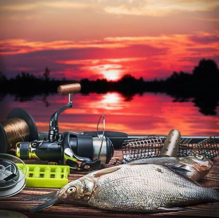 fishing tackle and caught fish on the table at sunrise photo