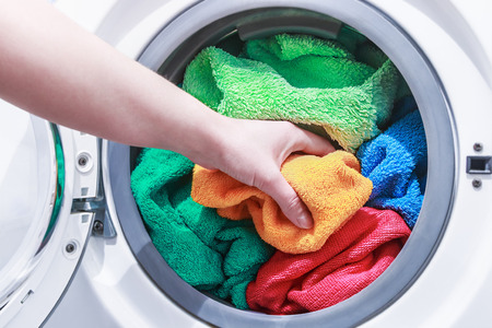 towel: hand and puts the laundry into the washing machine. focus on a colored towel
