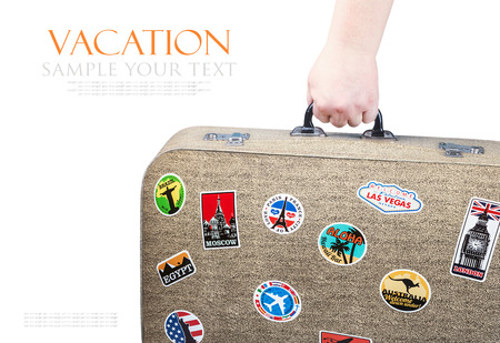 tex: hand holding a retro suitcase with stickers isolated on white background. Tex for example, and can be easily removed