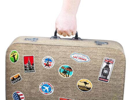 highway love: hand holding a retro suitcase with stickers isolated on white background.