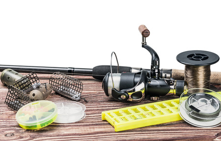 fishing gear: fishing tackle on a wooden table isolated on a white background Stock Photo