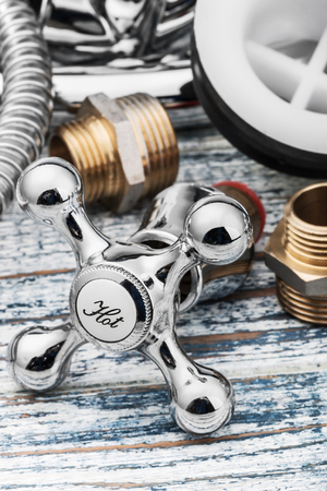 plumbing accessories: plumbing and accessories on wooden table. Focus on the word hot