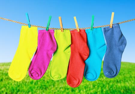 calcetas: calcetines de colores que cuelgan de una cuerda en el fondo de la naturaleza Foto de archivo