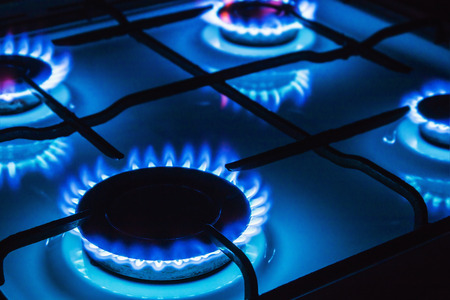stove: Burning blue gas. Focus on the front edge of the gas burners