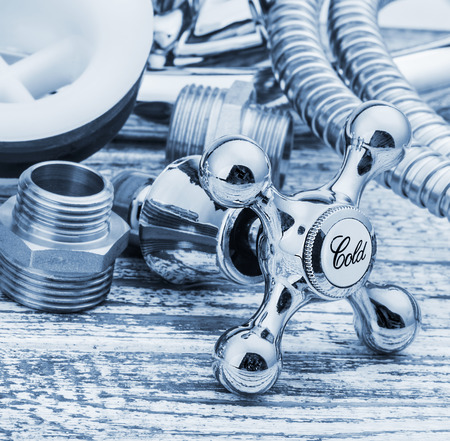 plumbing accessories: plumbing and accessories on wooden table. focus on the faucet with cold water