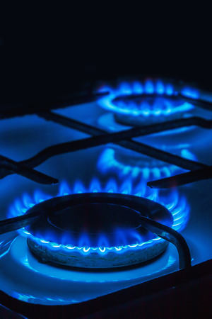 Burning blue gas. Focus on the front edge of the gas burners. black background from above can be used for your text