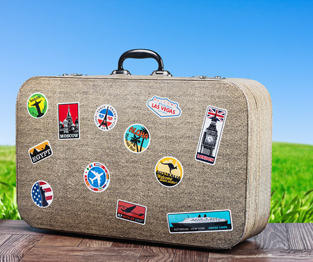 old travel suitcase on background with grass field. focus on a suitcase photo
