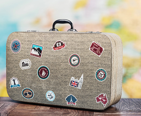 old suitcase with stikkers on the floor against the backdrop of a world map photo
