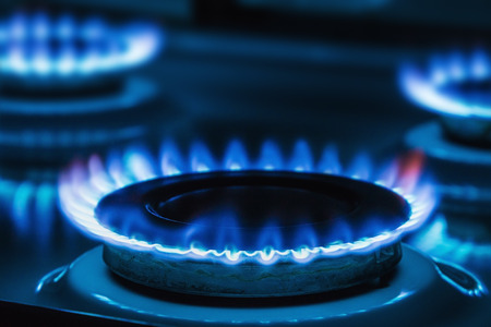 Burning blue gas on the stove. Focus on the front edge of the gas burners