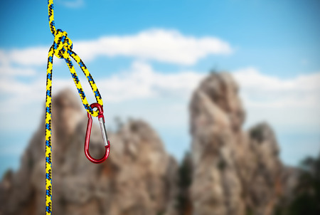 rappelling: rock climbing rope with hooks on a background of mountains