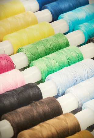 Multicolor sewing threads background. focus on the green thread. toning image