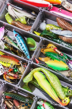 fishing gear: fishing lures and accessories in the box background. Focus in the center of the bait Stock Photo