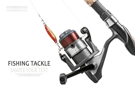 fishing reel: fishing tackle isolated on white. Focus on fishing lures, shallow depth of field. Text example Stock Photo