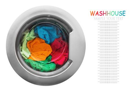 kleurrijke kleren in de wasmachine op een witte achtergrond. richten zich op wasgoed. Tekst voorbeeld Stockfoto