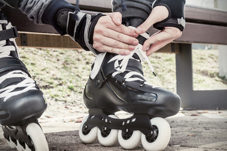 Close-up Of Legs Wearing Roller Skating Shoe. Focus on hands. toned image photo