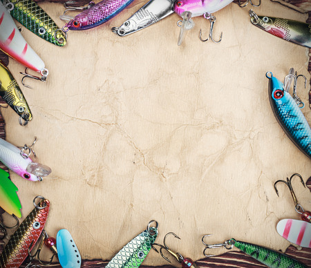 color image fish hook: Frame with spinner lures and fishing bait. Focus on paper and baits