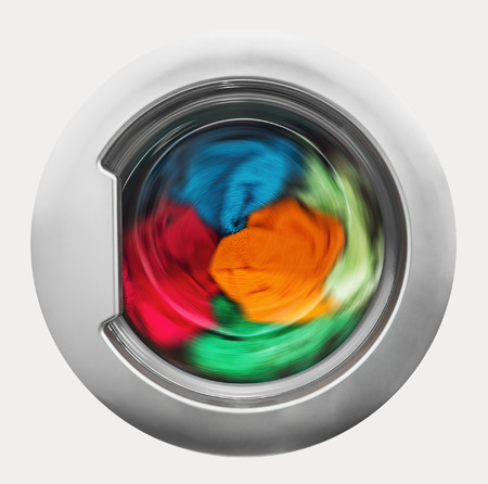 Washing machine door with rotating garments inside. focus in the center of dirty laundry and washing machine on the frame Stock Photo