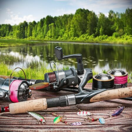 spinner: fishing tackle and accessories on the table against the background of a forest lake. Focus on spinning