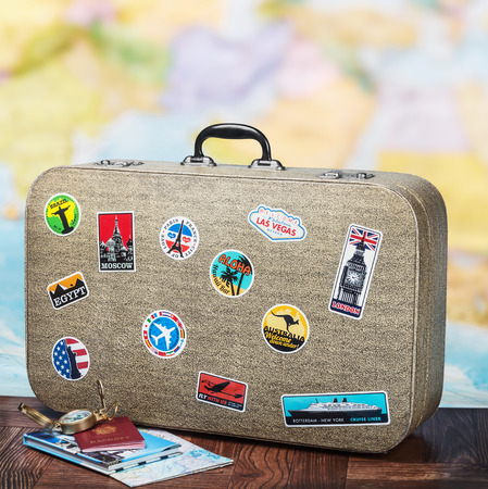 retro suitcase with stikkers on the floor against the backdrop of a world map