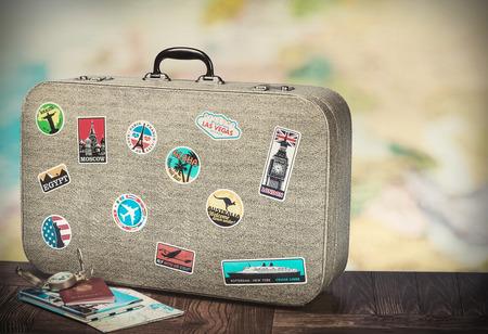 maletas de viaje: maleta retro con Stikkers en el suelo, contra el telón de fondo de un mapa del mundo. Imagen entonada Foto de archivo