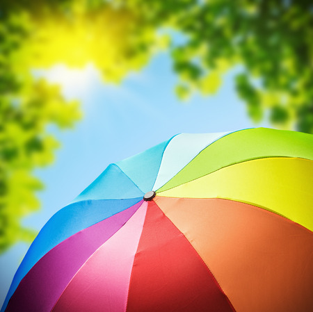 umbrella: Rainbow umbrellas against the backdrop of nature. focus on umbrella Stock Photo