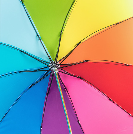 spokes: Colorful close up abstract of rainbow umbrella. Focus on the spokes of the umbrella