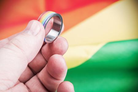 bandera gay: Anillo gay del arco iris en la palma de la comunidad en la bandera. Centrarse en la mano y el anillo Foto de archivo
